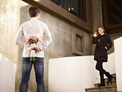 man waiting for girlfriend with flowers behind back