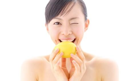 レモンをかじる女性