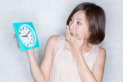 時計を見て焦る女性