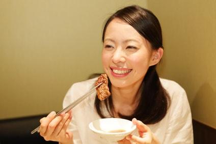 笑顔で焼肉を食べる女性