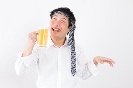 ビールを手に持ち頭にネクタイを巻いている酔っぱらいの男性