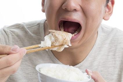 白米を肉で包み食べる男性