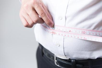 腹部周りを計測する男性