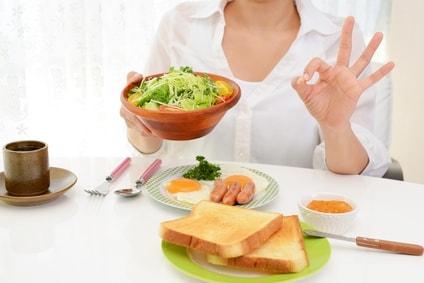 サラダの器を持ってOKサインを作る女性