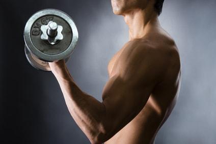 ダンベルで腕を鍛える男性
