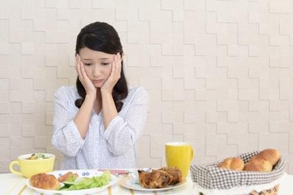 ダイエット中の女性が食事の前に悩んでいる