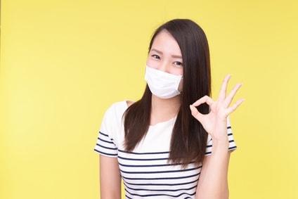 マスクをしてOKサインをしている女性
