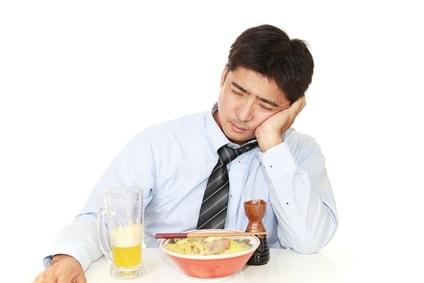 酔っぱらっているサラリーマンがラーメンを食べている