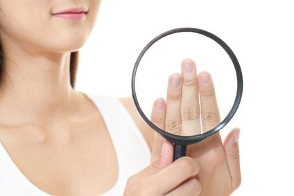 爪を虫眼鏡で見る女性